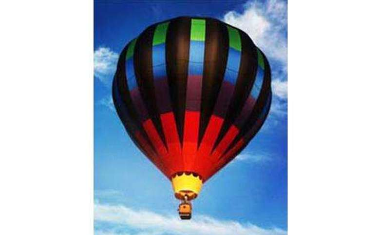 red, black, blue, and green hot air balloon in flight