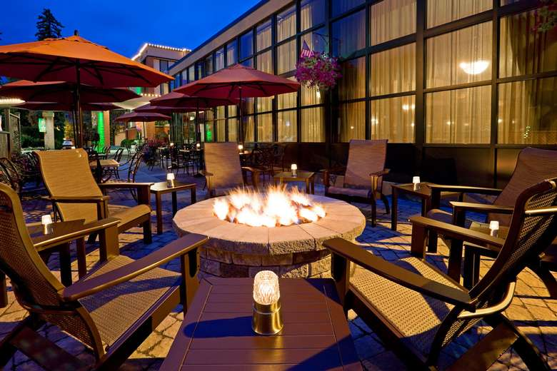 outdoor patio area with a fire pit surrounded by chairs