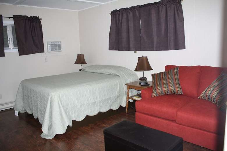 bed in room with white blanket, red couch