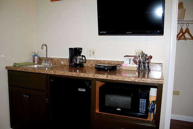 counter in room with coffee pot, hot plate, utensils, TV above, microwave underneath