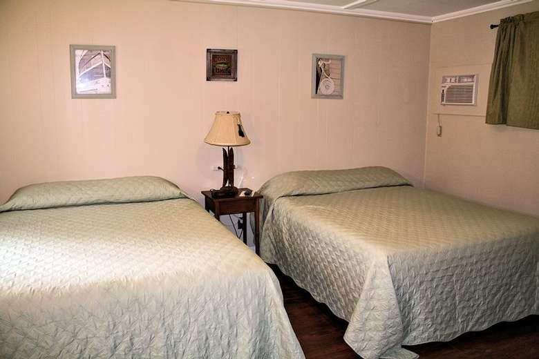 two beds in a bedroom, lamp on stand in between