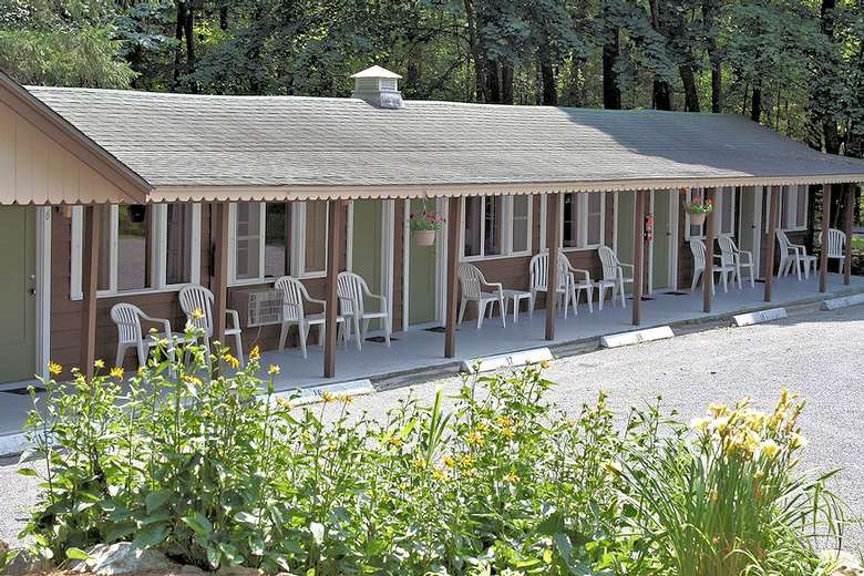motel unit with white chairs out front