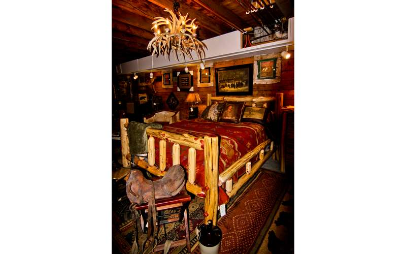 an Adirondack inspired bed with an antler chandelier above it