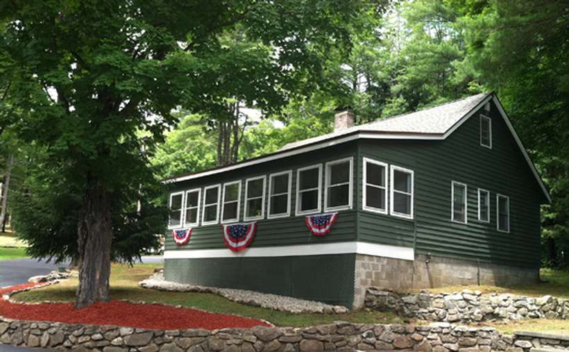 a green cottage with decorative American flags