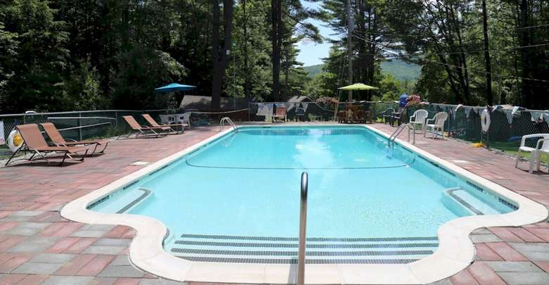 an outdoor pool, fenced in with chairs, surrounded by woods