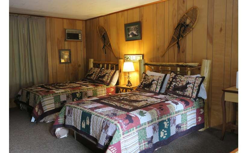two beds in a bedroom with a light on a stand in between them, snowshoes hanging above beds