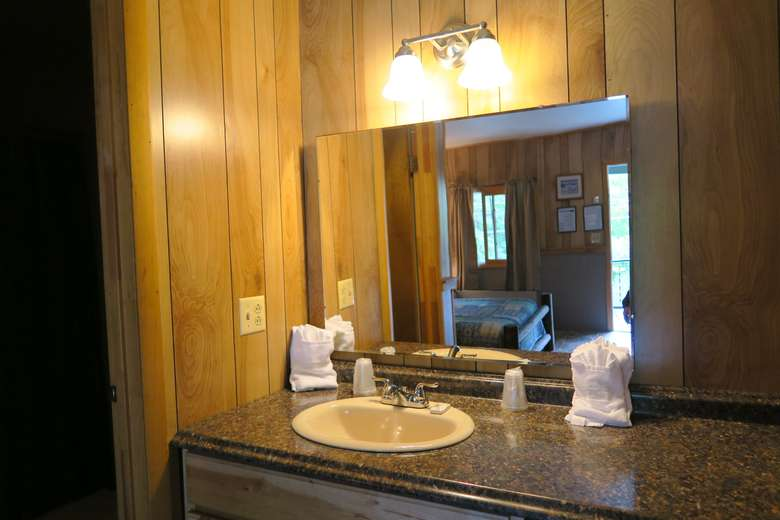 a bathroom sink with mirror and light above it