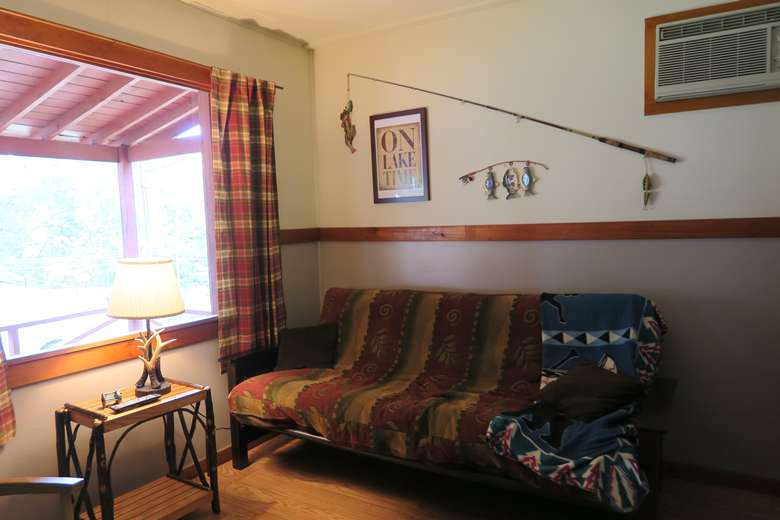 a futon with fishing decorations on the wall, sign that says On Lake Time