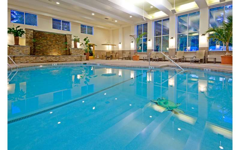 a large blue indoor pool with windows around it