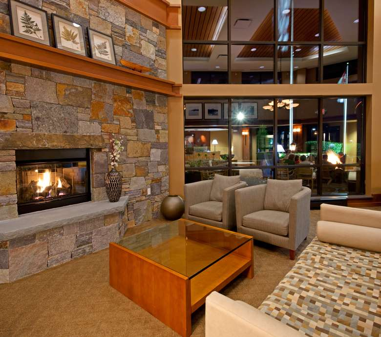 a lobby with a stone fireplace and gray chairs near the hotel entrance windows
