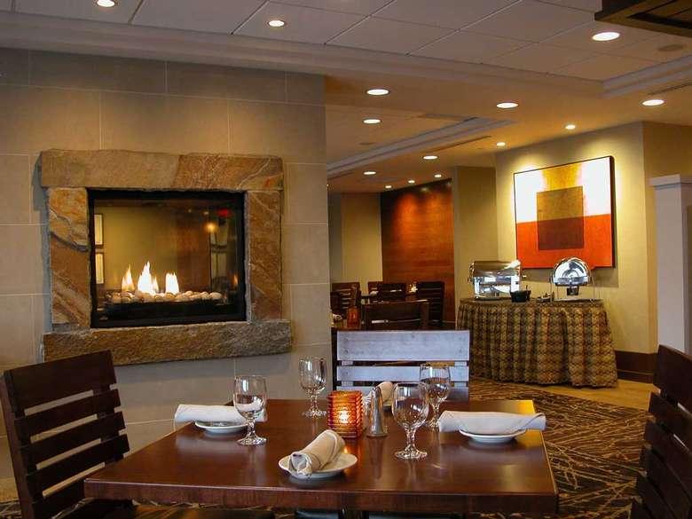 a restaurant table near a fireplace inside a hotel