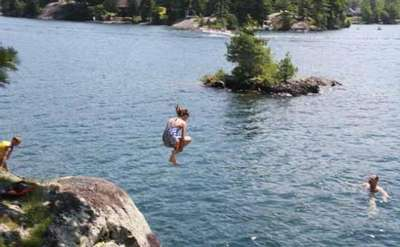 a girl jumping into the water from a cliff, and an island is in the background