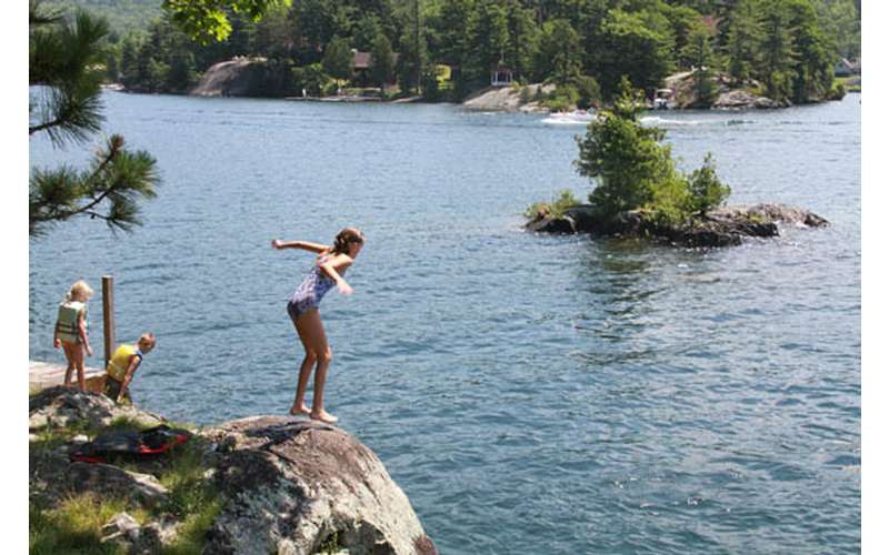 a girl preparing to jump from a cliff into a lake with an island in the background