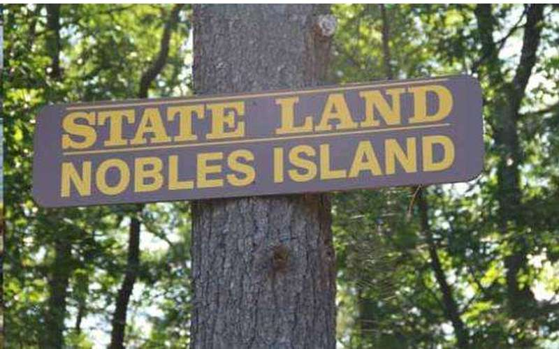 the sign for nobles island state land on a tree