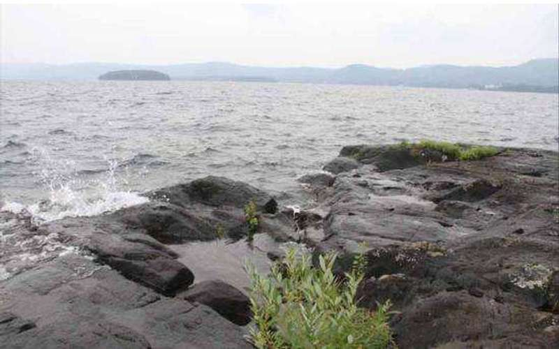 a rocky shoreline by a big lake