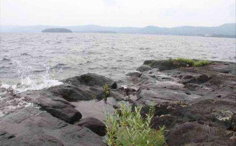 a rocky shoreline by a big lake