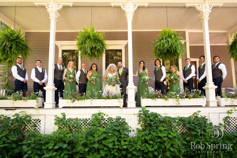 bridal party posing on a porch under large hanging ferns
