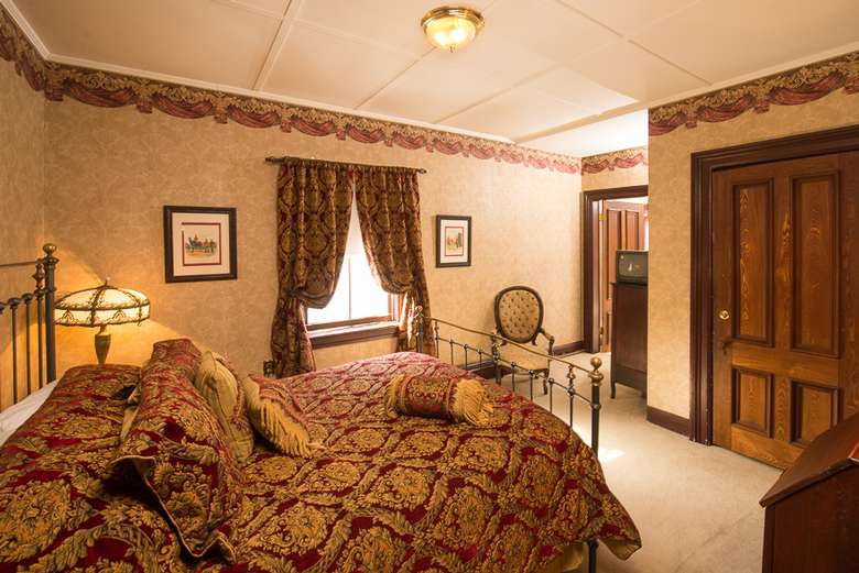 victorian style bedroom with a maroon and gold comforter and curtains