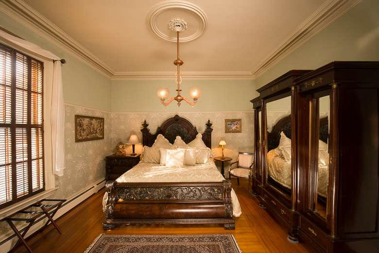 victorian style bedroom with a large wardrobe on the right side and a chandelier hanging over the bed