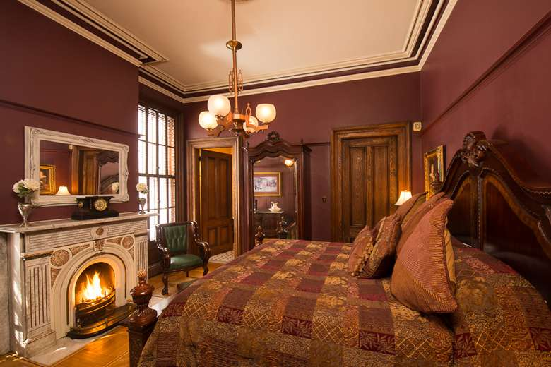 victorian style bedroom with maroon walls and a fireplace