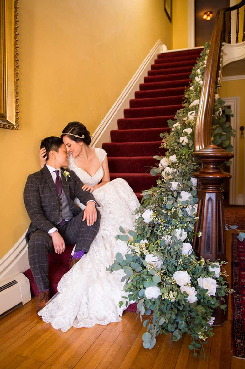 bride and groom sitting on a set of stairs