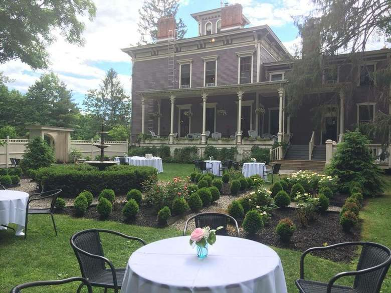 tables with tablecloths and chairs on the lawn of an inn