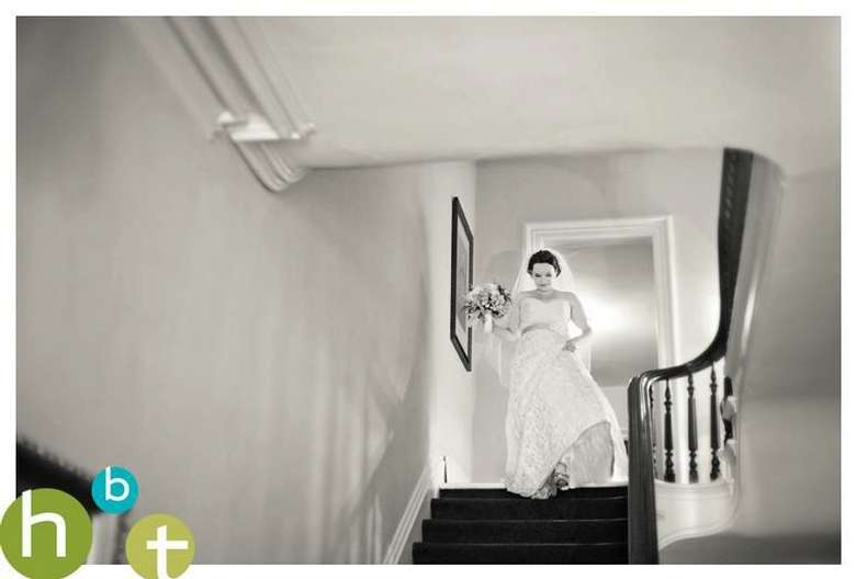 bride holding her bouquet and walking down the stairs