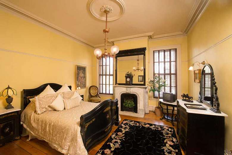 victorian style bedroom with yellow walls and a fireplace