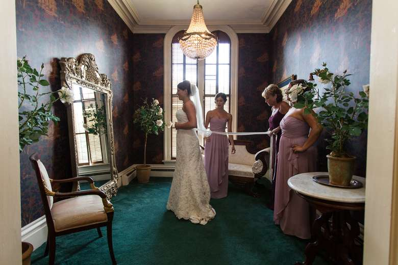 bridal party lacing the bride's dress while she admires herself in the mirror