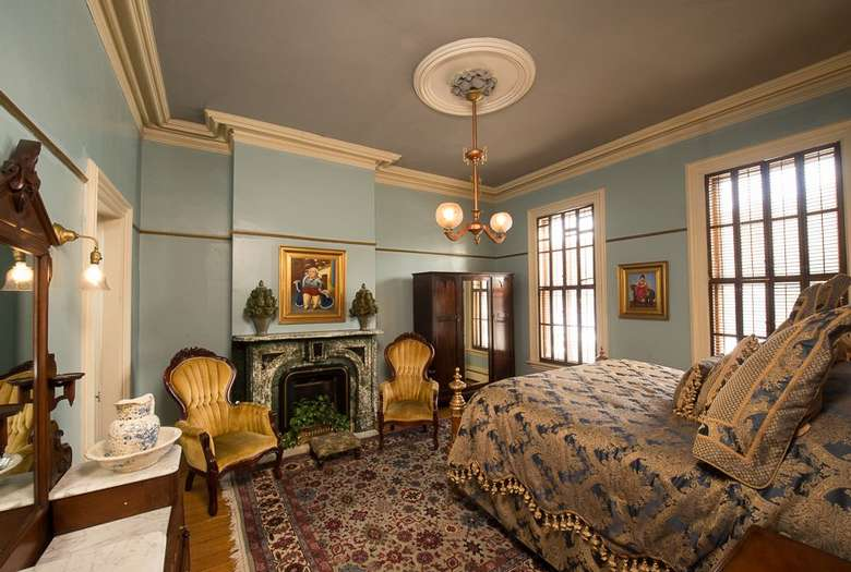 victorian style bedroom with light blue walls and gold velvet chairs