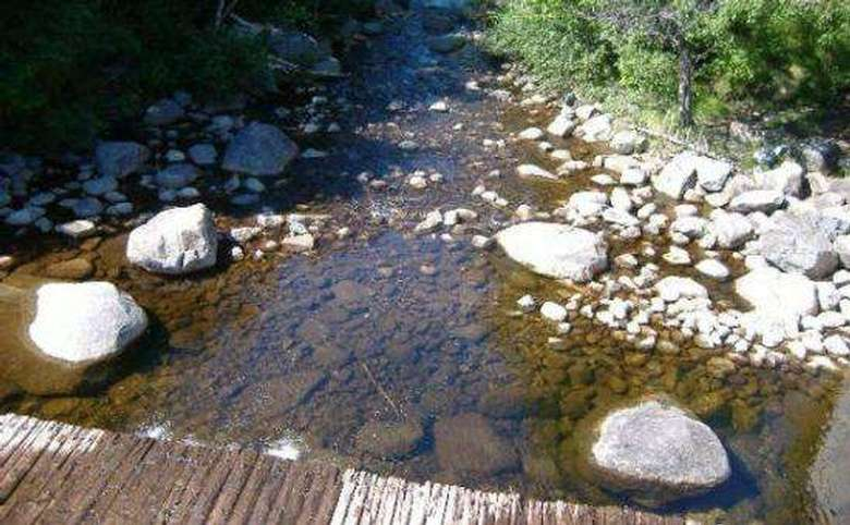 shallow stream with many rocks sticking out of it and a wooden bridge crossing it