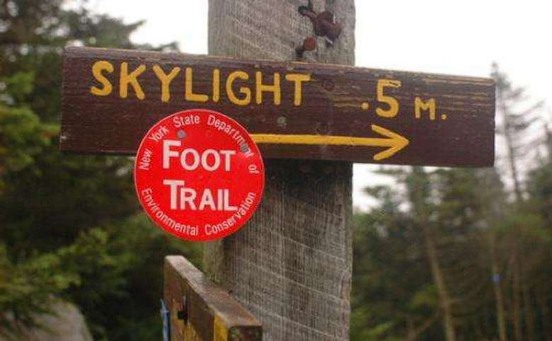 wooden sign that says skylight 0.5m with a red circular trail marker nailed to it