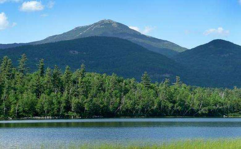 body of water in the foreground with whiteface mountain in the background
