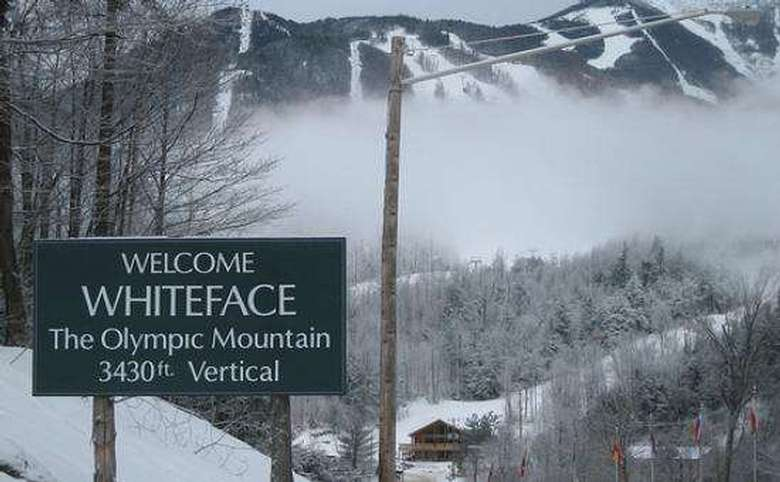 sign that says welcome whiteface the olympic mountain with a ski mountain visible in the background