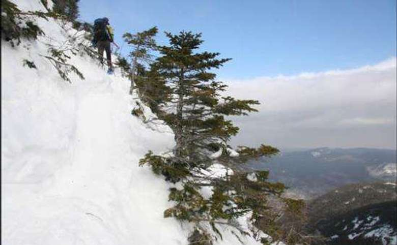 hiker climbing a steep mountain in the winter