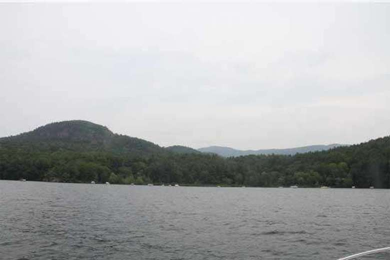 view from a boat of a shoreline with trees and mountains