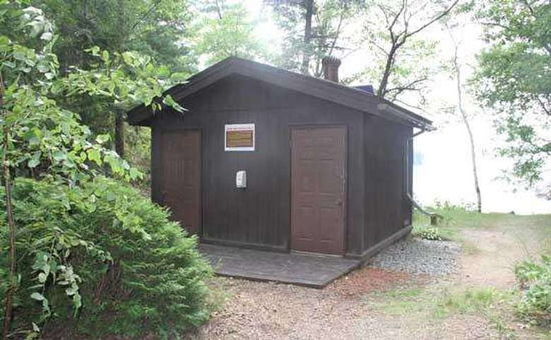 a small brown outhouse area with two doors