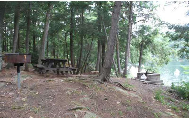 a campsite with a picnic table and grill on a small hill near the waterfront