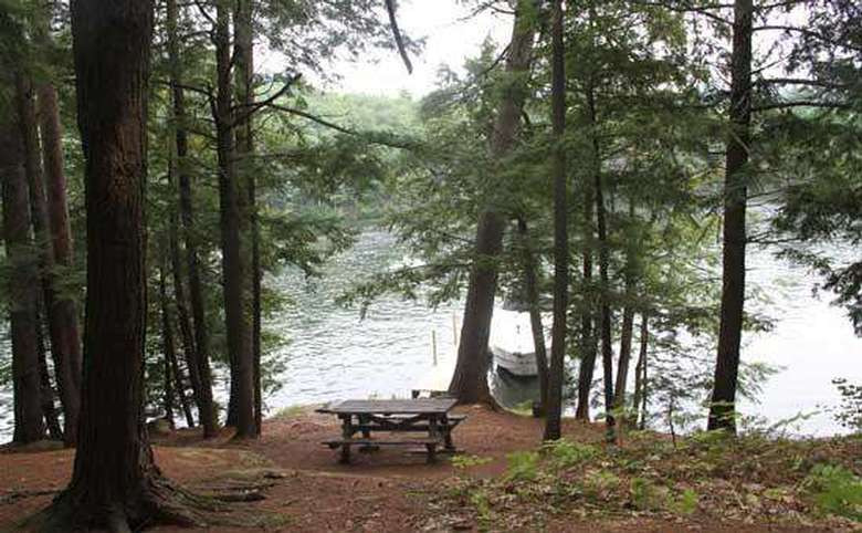 a picnic table close to the shoreline of a lake
