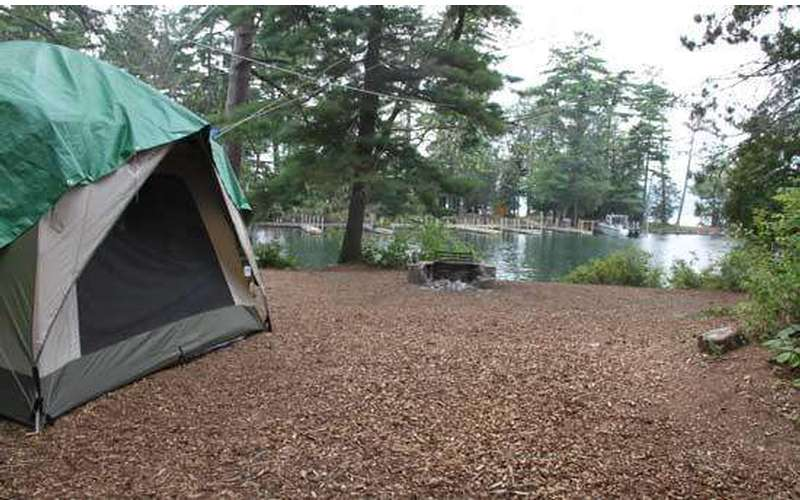 a green and grey tent at a fairly clear campsite with a fire pit at the edge of it