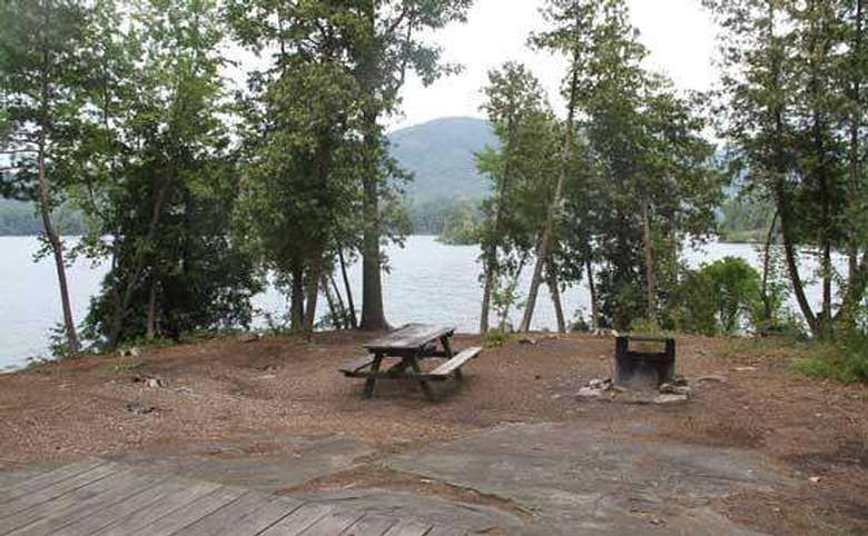 a flat campsite with a grill area, a picnic table, a tent platform, and the lake nearby