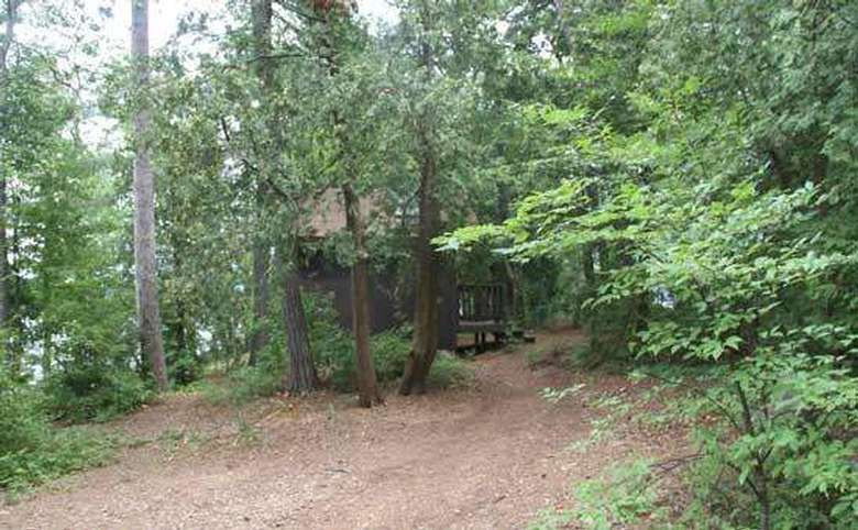a small wooden building near a campsite
