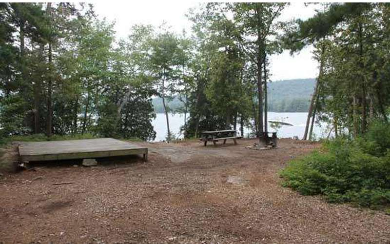 a tent platform and picnic table near the lakeside