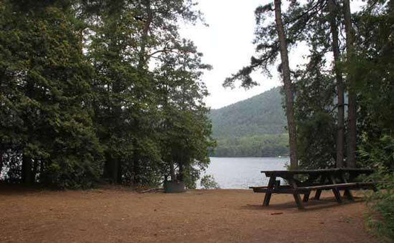 a dark picnic table on the waterfront with views of the lake and mountain in the background