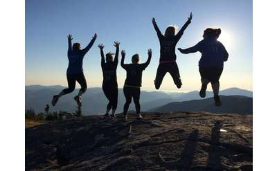 five women jumping at the top of cascade mountain