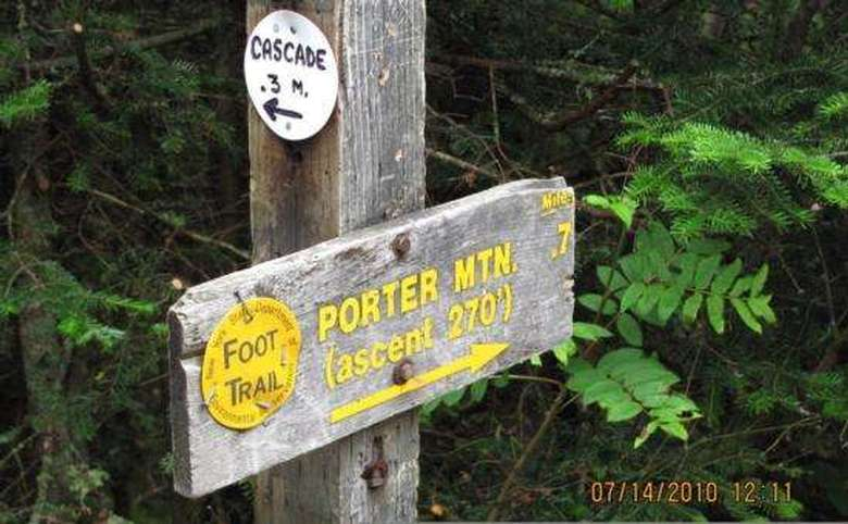 sign showing the route to the porter mountain summit with a yellow foot trail marker