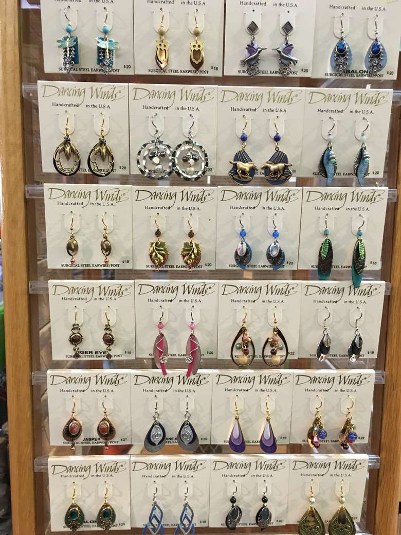 display of dancing winds earrings figurines at live love laugh