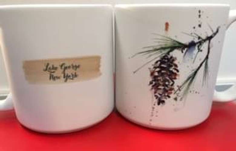 a coffee mug with a pine cone on one side and text that says lake george new york on the other