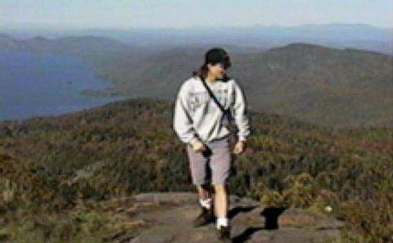 hiker nearing the top of a mountain summit