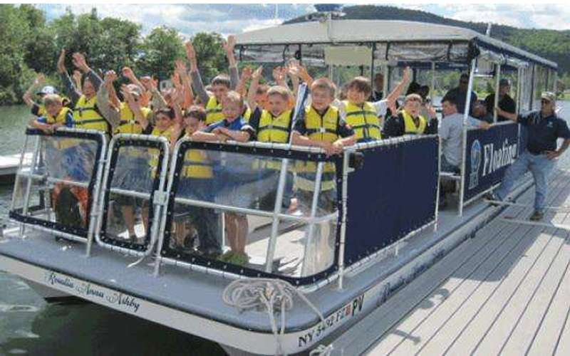 A group of kids in yellow life jackets waving from a boat